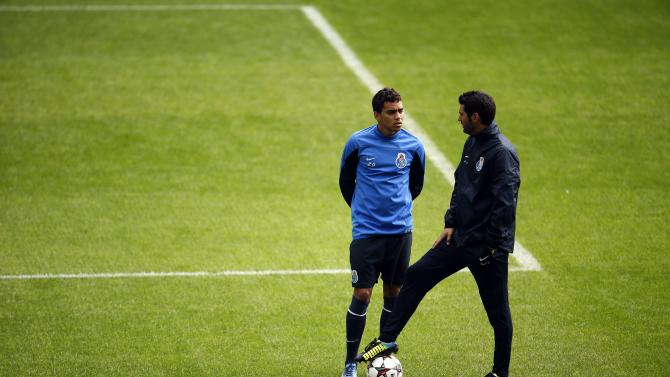 Porto's coach Paulo Fonseca speaks with player Carlos Eduardo during a training session at Dragon stadium in Porto