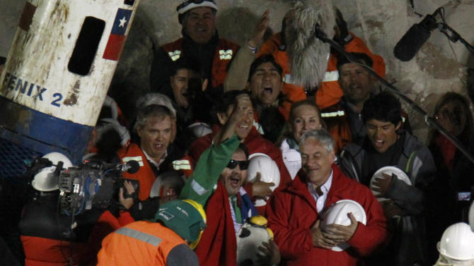 FILE - Luis Urzua, the last of the 33 miners to be rescued, center wearing green, celebrates next to Chile's President Sebastian Pinera after being pulled from the San Jose gold and copper mine near Copiapo, Chile. One of the myths surrounding the miners who survived 69 days, 700 feet deep, and whose unprecedented and dramatic rescue was beamed to millions around the world, is that they are millionaires and do not need work. A year after the tragedy, nearly half are unemployed, one lives the fame that began to take shape at the bottom of the mine, many have chosen to give motivational talks to make a living and four returned to work in the mines. (AP Photo/Roberto Candia, File)