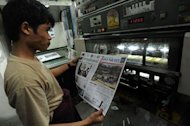 A worker monitors the printing of newspapers in Yangon, March 26, 2013. Privately owned daily newspapers hit Myanmar's streets for the first time in decades on Monday under new freedoms that represent a revolution for a media shackled under military rule