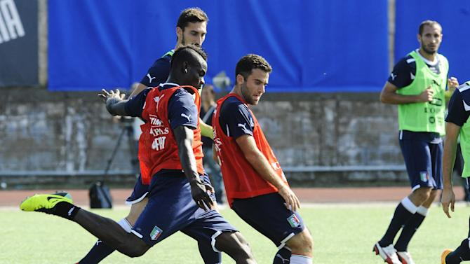 Italy's Mario Balotelli is flanked by Giuseppe Rossi, center, during a training session with their team at the Giarrusso stadium in the outskirts of Naples, Monday, Oct. 14, 2013, ahead of a 2014 FIFA World Cup, Group B, qualification match against Armenia in Naples on Tuesday.  Other teams in Group B are, Denmark, Bulgaria, Czech Republic, and Malta