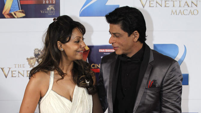In this Saturday, Jan. 21, 2012, file photo, Indian Bollywood superstar Shah Rukh Khan, right, poses with his wife, Gauri, on the red carpet of the Zee Cine Awards 2012 in Macau. Health officials in Mumbai are investigating reports that actor Khan has found out the sex of a child he is having through a surrogate mother. Sex determination tests are banned in India to stop the practice of aborting female fetuses due to a preference for sons. (AP Photo/Kin Cheung, File)