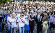 People march through the streets of the former Warsaw Ghetto during ceremonies marking the 70th anniversary of the start of Nazi Germany's mass deportation of Jews from the Warsaw Ghetto to the death camp of Treblinka