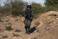 A Mexican soldier stands guard at a checkpoint on the road that links Navolato and Los Mochis, in Sinaloa State, Mexico, in January 2012. Police found 14 bodies in an abandoned van Thursday in northern Mexico, officials said, in what appeared to be the latest in a series of grisly killings linked to the country's brutal drug war