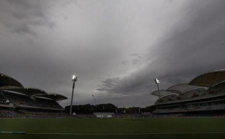 Storm clouds gather above the stadium during the fourth day's play in the second Ashes cricket test between England and Australia at the Adelaide Oval