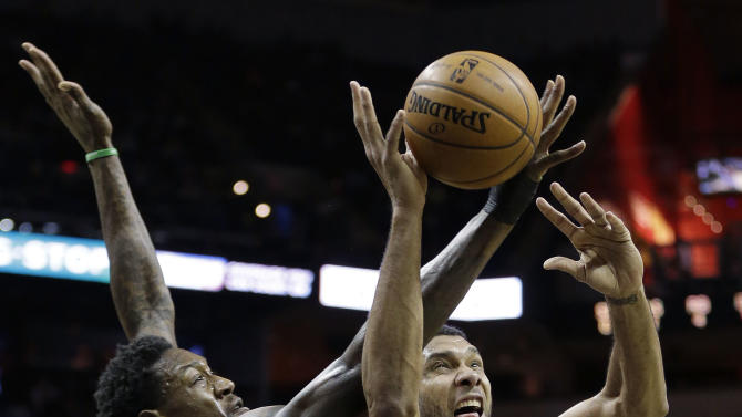 San Antonio Spurs' Tim Duncan (21) is defended by Milwaukee Bucks' Larry Sanders (8) while trying to score during the first half of an NBA basketball game on Sunday, Jan. 19, 2014, in San Antonio