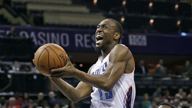 Charlotte Bobcats' Kemba Walker, left, drives past Philadelphia 76ers' Tony Wroten, right, during the first half of an NBA basketball game in Charlotte, N.C., Friday, Dec. 6, 2013
