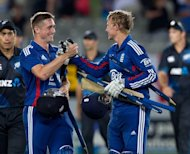 England's Chris Woakes (L) and Joe Root celebrate victory in the third and final one-day international against New Zealand in Auckland on February 23, 2013. Devastating bowling from Steven Finn and a solid top-order batting display gave England a five wicket win at Eden Park to claim the series 2-1