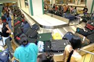 This file photo shows a group of Filipino domestic workers collect their bags from the carousel at Manila airport, in 2006. The Philippines said Sunday that at least 14 immigration officers were under investigation for alleged involvement in the human trafficking of poor Filipinos to violence-torn Syria