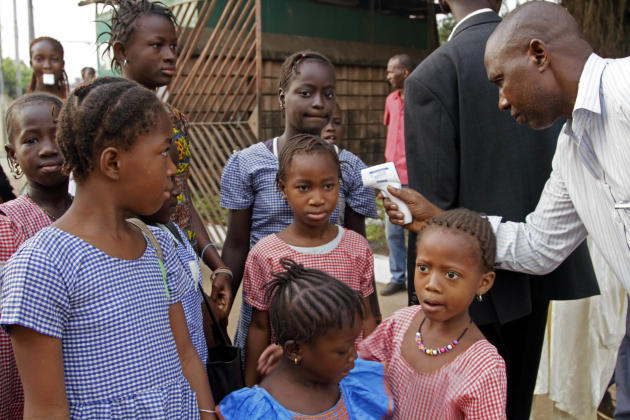 FILE In this Monday, Jan. 19, 2015 file photo, a health care worker, right, takes the temperatures of school children for signs of the Ebola virus before they enter their school in the city of Conakry