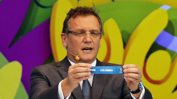 """FIFA Secretary General Jerome Valcke holds the slip showing """"Colombia"""" during the draw for the 2014 World Cup at the Costa do Sauipe resort in Sao Joao da Mata"""