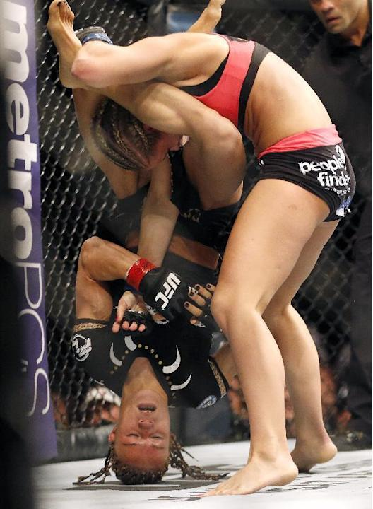 Felice Herrig, bottom, is lifted by Paige VanZant before being dropped during a UFC mixed martial arts bout, Saturday, April 18, 2015, in Newark, N.J. (AP Photo/Julio Cortez)