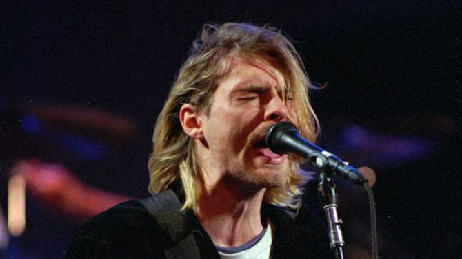 """FILE - This Dec. 13, 1993 file photo shows Kurt Cobain of the Seattle band Nirvana performing in Seattle, Wash. After hearing from Kurt Cobain and Nirvana fans across the United States, the Washington state city of Aberdeen is keeping the words """"Come as you are"""" on a welcome sign. KBKW and KXRO report Mayor Bill Simpson announced at Wednesday night's City Council meeting the sign will stay. The mayor received more than 300 emails after reports that the reference to a Nirvana song would be dropped when the sign is replaced. """"Come as you are"""" was added to the """"Welcome to Aberdeen"""" sign in 2005 following the 10-year anniversary of Cobain's 1994 death in Seattle. Cobain grew up in Aberdeen. (AP Photo/Robert Sorbo, file)"""
