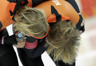 Ronald Mulder of the Netherlands, left, hugs his twin brother gold medallist Michel after the men's 500-meter speedskating race at the Adler Arena Skating Center during the 2014 Winter Olympics, Monday, Feb. 10, 2014, in Sochi, Russia. (AP Photo/Matt Dunham)