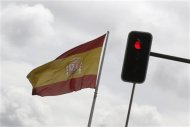 A Spanish national flag flies near a red traffic light in central Madrid