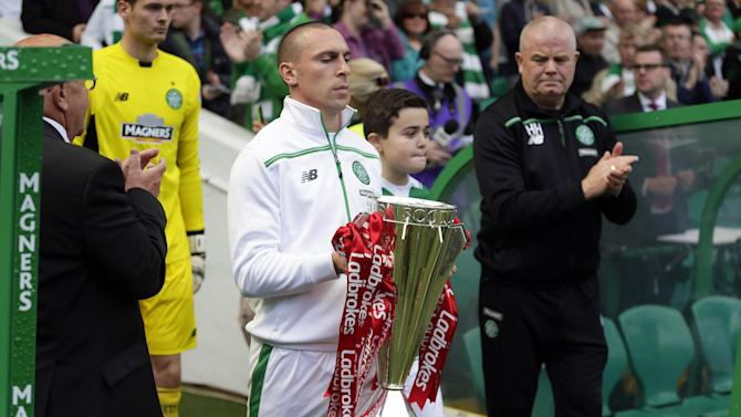 Celtic's Scott Brown (L) brings out the Premiership trophy before the match