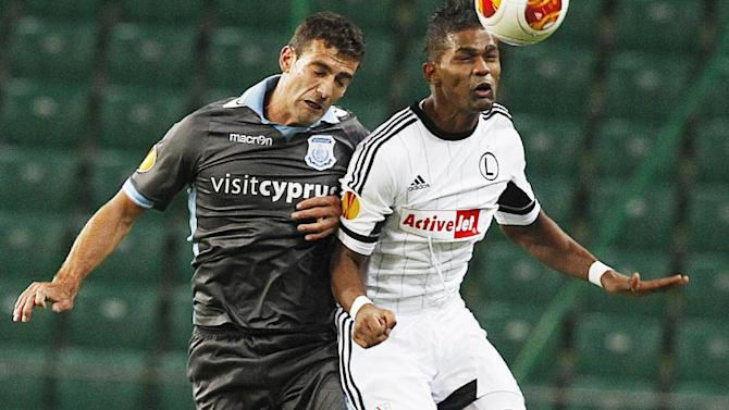 Roberto, left, of Apollon Limassol FC challenges for the ball with Dossa Junior, right, of Legia Warsaw, during their Europa League group J soccer match in Warsaw, Poland, Thursday, Oct. 3, 2013