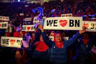 Supporters of the ruling National Front coalition, or Barisan Nasional, wave banners during a rally at a stadium in Bukit Jalil, a suburb of Kuala Lumpur, on April 6, 2013. Malaysia's premier Najib Razak unveiled a manifesto on Saturday pledging bigger cash handouts, millions of new jobs and lower taxes and crime, as he seeks his first mandate in looming national polls
