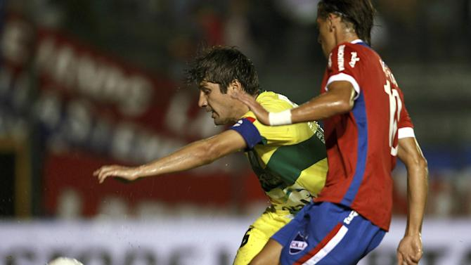 Ronald Raldes of Bolivia's Oriente Petrolero, left, fights for the ball with Richard Porta of Uruguay's Nacional during a Copa Libertadores soccer match in Santa Cruz, Bolivia, Tuesday, Jan. 28, 2014