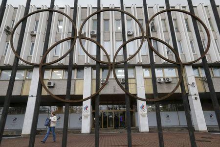 A woman walks out of the Russian Olympic Committee headquarters building in Moscow