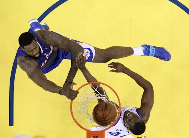 Los Angeles Clippers' DeAndre Jordan, top, dunks over Golden State Warriors' Harrison Barnes during the first half in Game 3 of an opening-round NBA basketball playoff series on Thursday, Apri