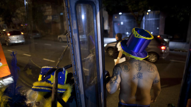 "A member of the murga ""Los amantes de La Boca"" stands on bus as he heads to carnival celebrations in Buenos Aires, Argentina, Saturday, Feb. 2, 2013. Argentina's carnival celebrations may not be as well-known as the ones in neighboring Uruguay and Brazil, but residents of the nation's capital are equally passionate about their ""murgas,"" or traditional musical troupes. The murga ""Los amantes de La Boca,"" or ""The Lovers of The Boca"" is among the largest, with about 400 members. It's a reference to the hometown Boca Juniors, among the most popular soccer teams in Argentina and the world. In background, Boca Juniors soccer team's stadium. (AP Photo/Natacha Pisarenko)"