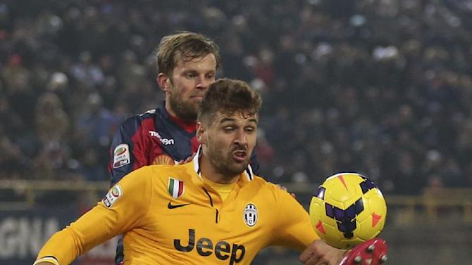 Juventus' Fernando Llorente, controls the ball ahead of Bologna defender Mikael Antonsson, of Sweden, during the Serie A soccer match between Bologna and Juventus at the Dall' Ara stadium in Bologna, Italy, Friday, Dec. 6, 2013