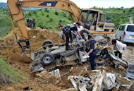 This file photo, taken on November 25, 2009, shows police investigators looking for evidence next to a backhoe, on a mangled vehicle unearthed at the crime scene where human remains were dug up from a shallow grave as investigators try to find more bodies, victims of a massacre after gunmen shot people in the town of Ampatuan, Maguindanao province in the southern Philippines