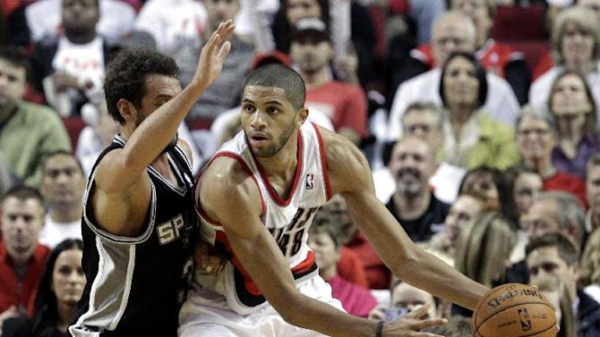 Portland Trail Blazers forward Nicolas Batum, right, from France,  looks to pass against San Antonio Spurs guard Marco Belinelli, from Italy, during the second half of an NBA basketball game in Portland, Ore., Saturday, Nov. 2, 2013. Batum   scored a triple-double as they defeated the Spurs 115-105
