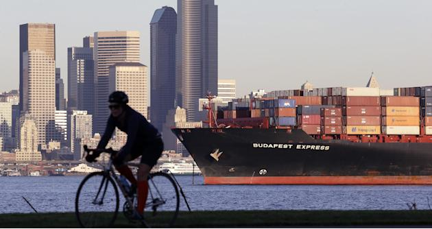 FILE - In this Nov. 17, 2014 file photo, a bicyclist rides in view of a loaded container ship anchored in Elliott Bay near downtown Seattle. The Commerce Department releases international trade data f