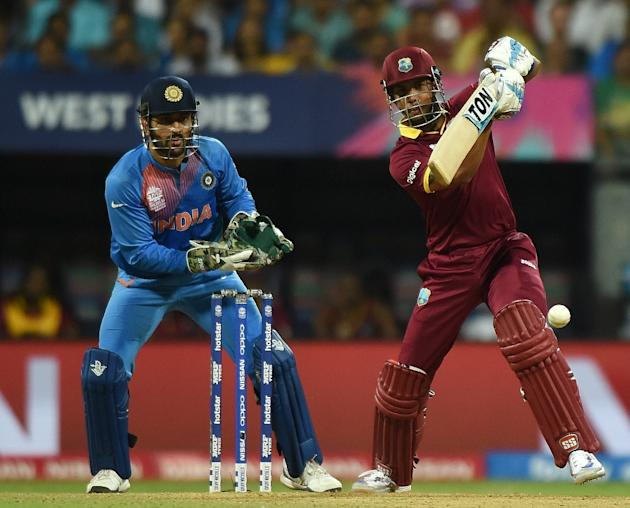 West Indies batsman Lendl Simmons plays a shot as India's captain Mahendra Singh Dhoni looks on during the World T20 semi-final at the Wankhede Stadium in Mumbai on March 31, 2016