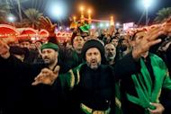 Shiite Muslims gather outside the shrine of Imam Abbas in Karbala early on Sunday. Throngs of pilgrims beat their chests and some used swords to make cuts on their heads as a sign of mourning for Imam Hussein, grandson of the Prophet Mohammed who was killed in 680 AD by the armies of the caliph Yazid.