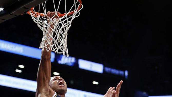 Utah Jazz's Richard Jefferson, left, grabs the rim after missing a dunk against Brooklyn Nets' Brook Lopez, right, during the second half of an NBA basketball game Tuesday, Nov. 5, 2013, in New York. Brooklyn defeated Utah 104-88