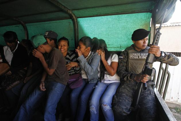 Youth and a soldier travel in a military truck on their way to participate in a social programme in Tegucigalpa