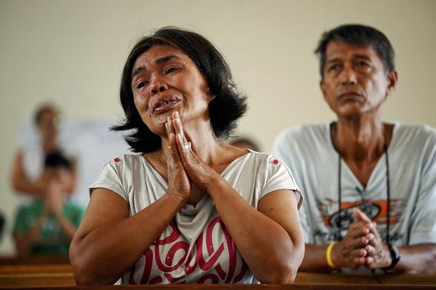 Rosario Capidos cries thanking God that she and her family survived typhoon Haiyan as she prays during Sunday Mass at the damaged Santo Nino Church in Tacloban November 17, 2013. Mobbed by hungry villagers, U.S. military helicopters dropped desperately needed aid into remote areas of the typhoon-ravaged central Philippines, as survivors of the disaster flocked to ruined churches on Sunday to pray for their uncertain future. The Philippines is facing up to an enormous rebuilding task from Typhoon Haiyan, which killed at least 3,681 people and left 1,186 missing, with many isolated communities yet to receive significant aid despite a massive international relief effort. REUTERS/Damir Sagolj (PHILIPPINES - Tags: SOCIETY DISASTER RELIGION)