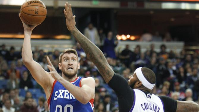 Philadelphia 76ers center Spencer Hawes (00) shoots over Sacramento Kings defender DeMarcus Cousins (15) during the first half of an NBA basketball game in Sacramento, Calif., on Thursday, Jan. 2, 2014
