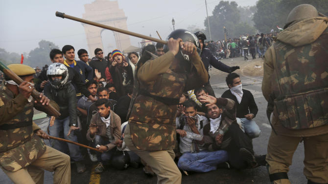 Protesters shield themselves as police prepare to beat them with sticks during a violent demonstration near the India Gate against a gang rape and brutal beating of a 23-year-old student on a bus last week, in New Delhi, Sunday, Dec. 23, 2012. The attack last Sunday has sparked days of protests across the country. (AP Photo/Kevin Frayer)