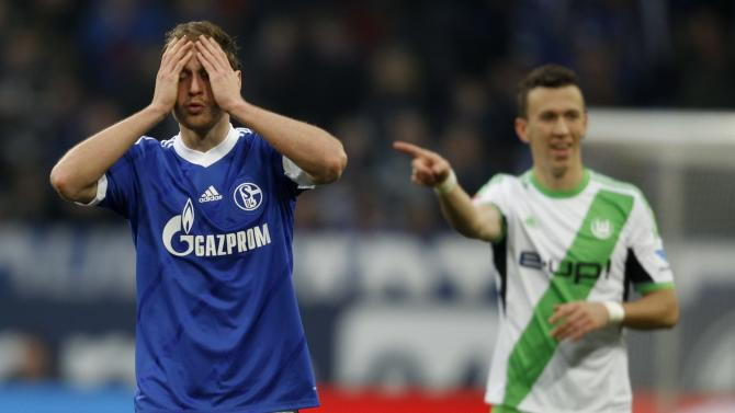 Schalke 04's Hoewedes reacts, while Wolfburg's Perisic points during the German first division Bundesliga soccer match in Gelsenkirchen