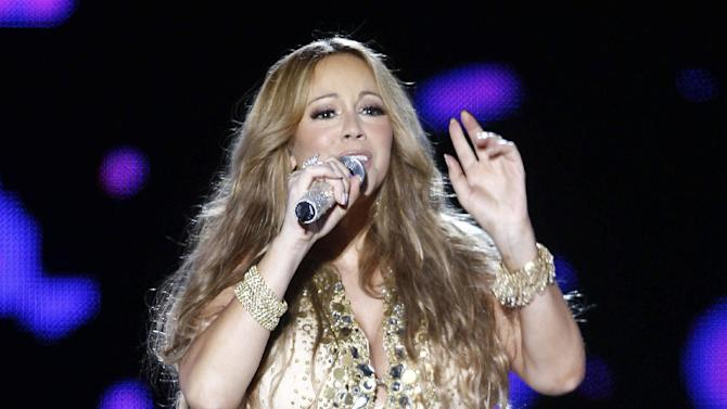 """FILE - This May 26, 2012 file photo shows U.S. Singer Mariah Carey performing on stage during a concert at the Mawazine Festival in Rabat, Morocco. A person familiar with the singing competition series """"American Idol""""  negotiations say Carey is being pursued to join the judging panel of the Fox talent competition. The source requested anonymity because of the private nature of negotiations. (AP Photo/Abdeljalil Bounhar, file)"""