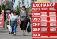 Pedestrians walk past an exchange office's rates notice in Bucharest August 10. The recovery in Romania's economy after two years of severe recession is now coming under threat, analysts warn, victim to the months-long political crisis that has engulfed the EU country