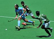 Captain Sadar Singh of India (left) runs through Muhammad Waqas and Haseem Abdul Khan of Pakistan during the bronze medal match at the men's Hockey Champions Trophy tournament in Melbourne. Australia went some way to erasing the pain of their London Olympics flop by winning a record fifth consecutive Champions Trophy in a 2-1 extra-time victory over the Netherlands