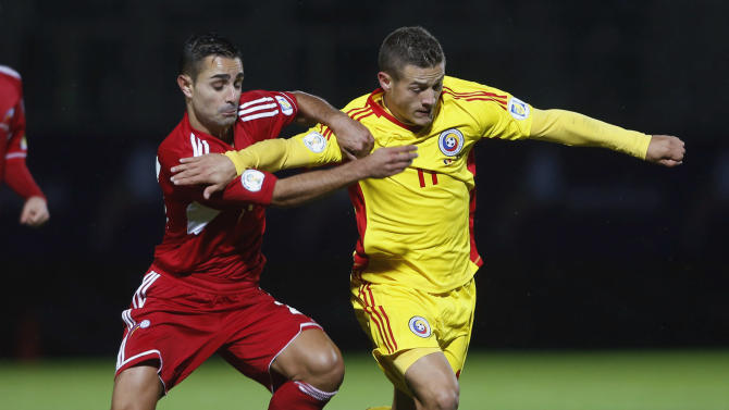 Romania's Torje fights for the ball with Andorra's Garcia during their 2014 World Cup qualifying soccer match at Estadi Comunal in Andorra