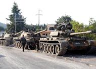 A picture released by the Syrian Arab News Agency (SANA) on August 8, 2013 shows Syrian army tanks parked on the side of a road during an alleged pursuit of opposition fighters in the Latakia province, western Syria. Troops loyal to President Bashar al-Assad drove rebels out of his Latakia home province Monday as UN inspectors began probing the alleged use of chemical weapons in the Syria war