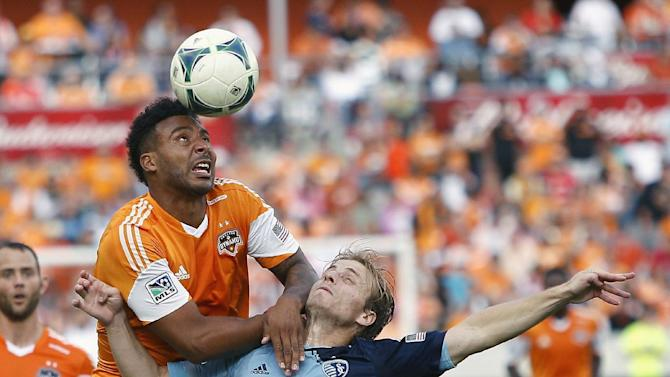 Houston Dynamo's Giles Barnes, left, heads the ball away from Sporting KC defender Seth Sinovic, right, during the second half of the MLS Eastern Conference soccer final on Saturday, Nov. 9, 2013, in Houston
