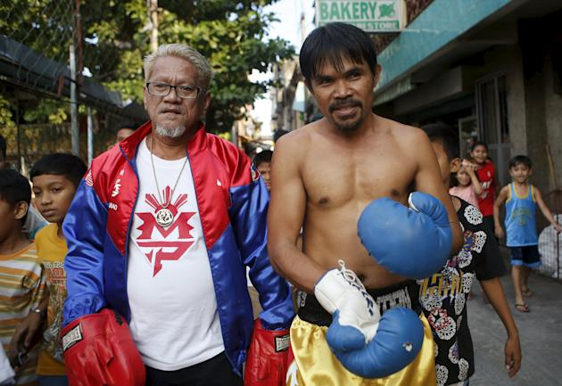 "World Boxing champion Manny Pacquiao look-alike Johnny Dagami walks with his ""trainer"" at their neighbourhood in Las Pinas, Metro Manila"