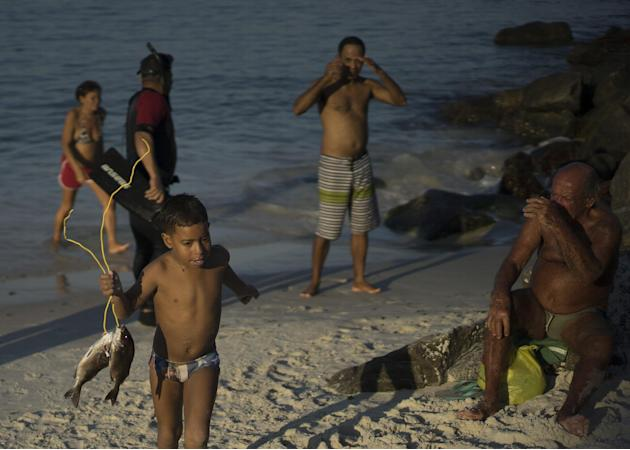 In this July 12, 2015 photo, a boy walks with his father's catch of the day from the Marina da Gloria, in Rio de Janeiro, Brazil. The head of Rio's Infectious Diseases Society said contaminate