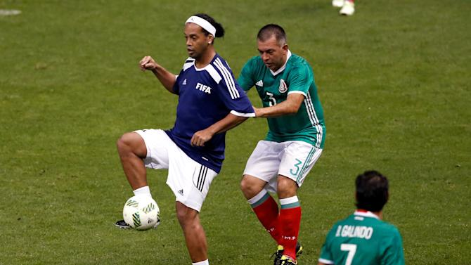 Ronaldinho of Brazil fights for the ball with de Dios Ram'rez of Mexico during a friendly soccer match between FIFA Football Legends against Mexican all-stars at Azteca stadium in Mexico City
