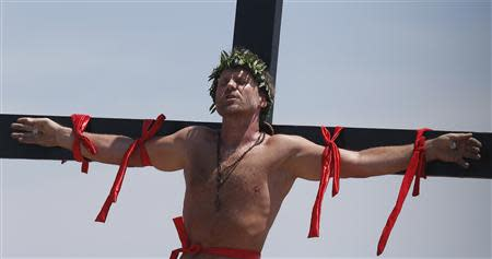 Danish filmmaker Olsen utters words as he is crucified on a wooden cross during a Good Friday ritual of the re-enactment of the death of Jesus Christ in San Fernando