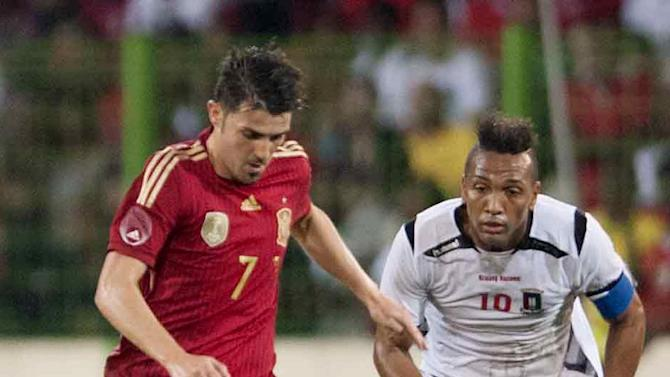 Spain's David Villa, left, in action with  Equatorial Guinea's Emilio Nsue, right, during their friendly soccer match at Malabo Stadium in Malabo, Equatorial Guinea, Saturday, Nov. 16, 2013