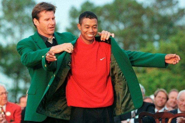 Nick Faldo slips Tiger Woods into the Green Jacket for the first time