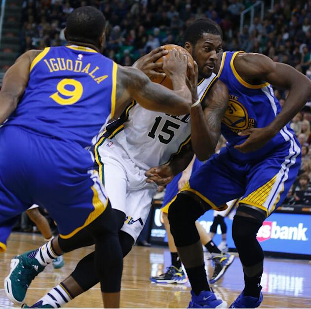 Utah Jazz forward Derrick Favors (C) is challenged by Golden State Warriors' Andre Iguodala (L) and Festus Ezeli during their game November 30, 2014 at Vivint Smart Home Arena